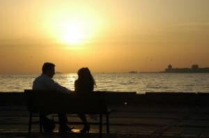 couple-sitting-on-a-bench-at-sea-sunset_2783103